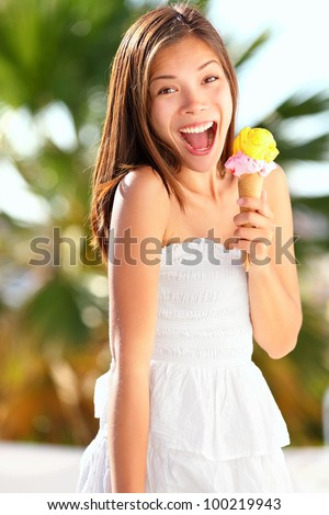 Ice cream girl excited and happy eating ice cream cone on beach during summer vacation. Lovely sweet mixed race Asian Chinese / Caucasian young woman outside.