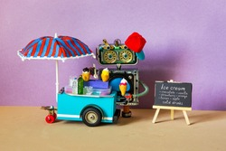 Ice cream mobile cart. Summer shop with big umbrella. Funny robot shopman sell ice cream and cold lemonade drinks. Green background. copy space black chalkboard menu.