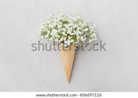 Ice cream of gypsophila flowers in waffle cone on light gray table top view in flat lay style