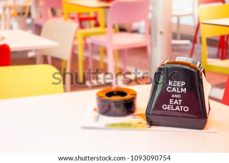 """Ice Cream parlor restaurant table with napkin holder advertising """"keep calm and eat gelato"""" #1093090754"""