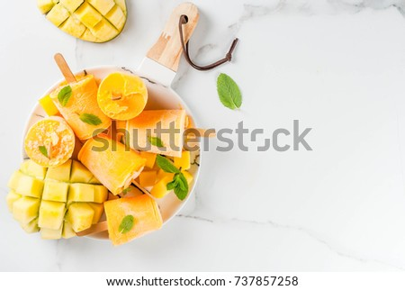 Ice cream, popsicles. Organic dietary foods, desserts. Frozen mango smoothie, with mint leaves and fresh mango fruit, on plate, on white marble table. Copy space top view