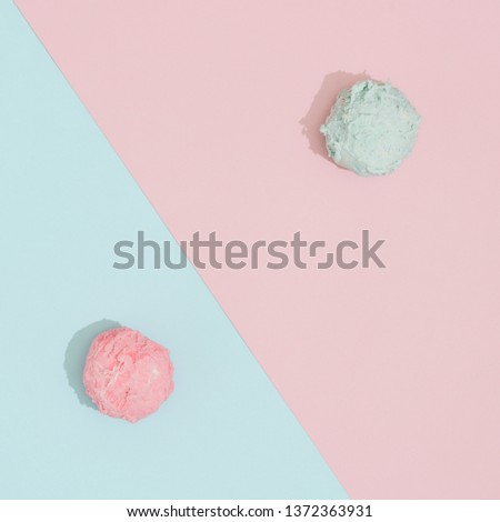 Ice cream scoops on pastel pink and blue background. Minimal summer food concept. Flat lay.