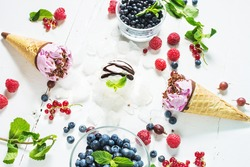 ice cream scoops with fresh berries on white wood background