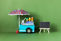 Ice cream toy cart with blue red umbrella. Assortment of ice cream empty menu black chalkboard. Summer vacation concept. Green background