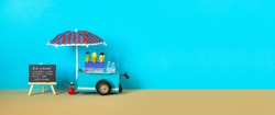 Ice cream toy cart with blue red umbrella. Assortment of ice cream menu black chalkboard. Summer vacation concept. Blue sandy beach background. copy space.