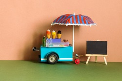 Ice cream toy cart with blue red umbrella. Empty menu black chalkboard. Summer street food business concept