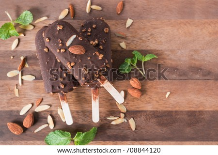 Ice cream vanilla bar covered with chocolate and almonds sticks. Popsicle and lolly sweet dessert. Top view and Copy space.