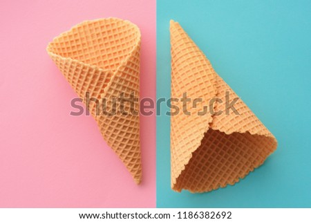 Ice cream waffle cones on pastel pink and blue background, top view flat lay modern minimal composition