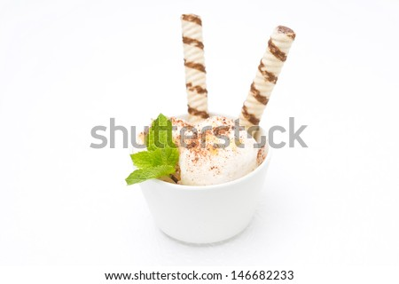 ice cream with ginger and chocolate, decorated with waffles and mint on white background - stock photo