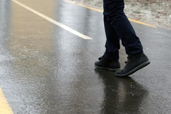 Ice crusted ground, a man walking on a slippery street, icy sidewalk, winter weater