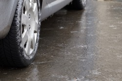 Ice crusted ground, car wheel on icy road, hazardous weather conditions, winter street