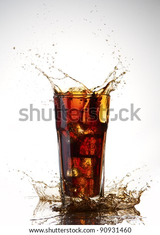 Ice cube dropped in cola glass and cola splashing