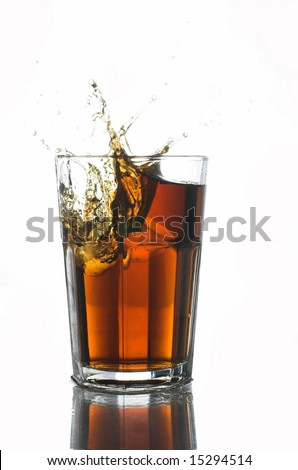 ice cube falling into a glass of coke - stock photo