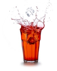 Ice cube falling into a red beverage splashing on white background.