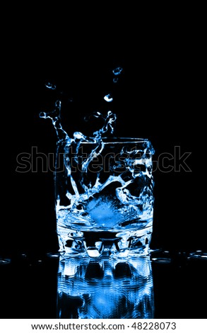 Ice cube splashing into glass of water, isolated on black