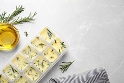 Ice cube tray with herbs frozen in oil and fresh rosemary on grey table, flat lay. Space for text
