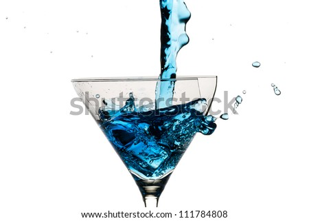 Ice cubes and martini glass filled with blue liqueur on white background