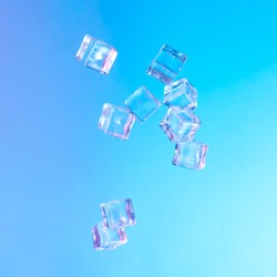 Ice cubes in vibrant bold gradient purple and blue holographic color lights. Concept art. Minimal summer surrealism.