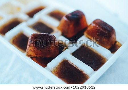 Ice cubes made with coffee in ice cube tray to prepare refreshing coffee drinks, close up on white background
