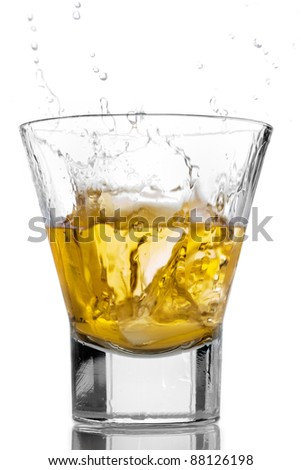 Ice cubes splashing into a glass of whiskey