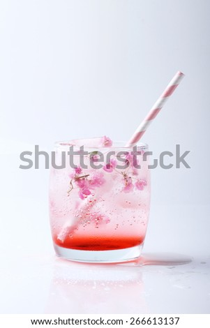 Ice cubes with pink flowers in glass  with paper straw on white background