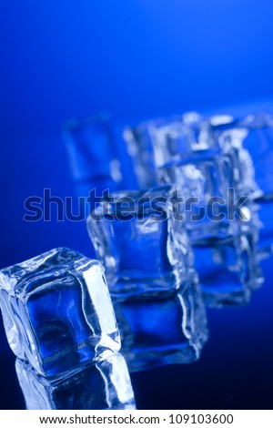 Ice cubes with reflection on blue background