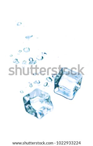 ice cubes with water splashes isolated on white background. Water splash with ice cubes. Ice cubes fall into the water causing bubbles.  #1022933224