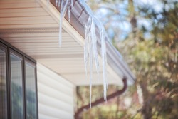 Ice dam in gutter and ice frozen on roof in winter, shallow focus on icicles