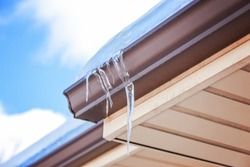 Ice dam in gutter and icicles frozen on roof in winter, focus on icicle