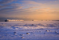 ice dunes and ice covered break walls along the shoreline of Lake Erie. Epic colorful dawn sky during winter