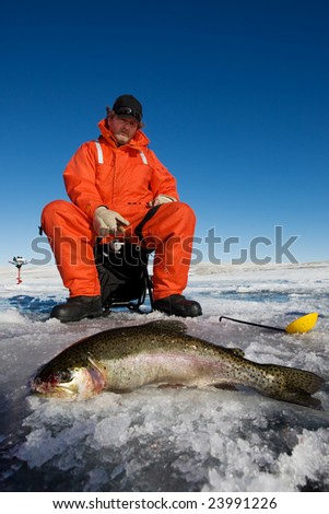 Ice fisherman with a large rainbow trout on the ice
