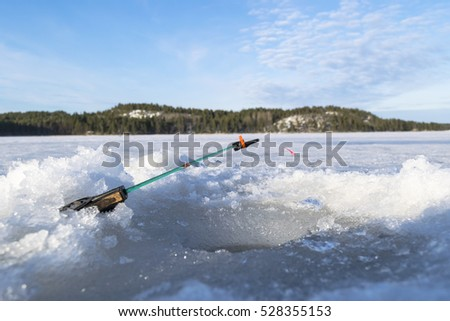 ice fishing rod with the line at ice near the hole, hobby #528355153