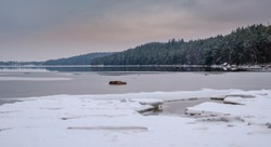 Ice floe at the beach with forest in the background on the other side of the lake