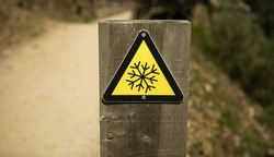 Ice hazard sign. Triangular yellow sign of low temperatures or ice formations.