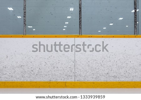 Ice hockey arena boards with puck marks.