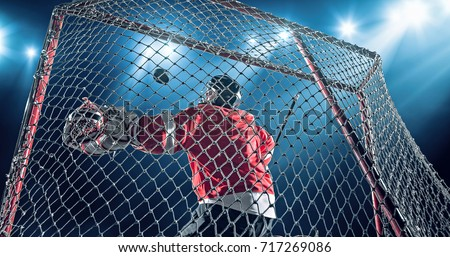 Ice Hockey goalie saves a goal on a dark background with intensional lens flares. He is wearing unbranded sports clothes.
