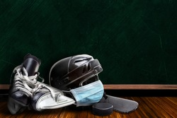Ice hockey helmet wearing surgical mask on a background chalk board with copy space for text. Concept of COVID-19 coronavirus pandemic affecting ice hockey season due to game or league suspensions.