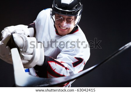 Ice-hockey player holds stick