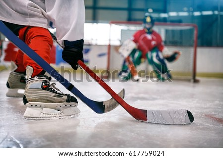 ice hockey player in action kicking with stick on goal