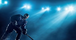 Ice Hockey player is skating on a abstract background with intensional lens flares. He is wearing unbranded sports clothes.