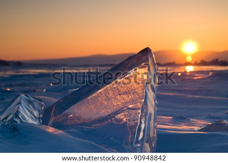 Ice hummock with flash of light at ice of lake Baikal on sunset