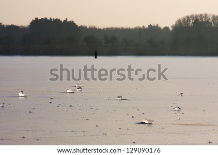 Ice lake with two men fishing under ice in the back ground