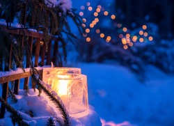 Ice lanterns, used as a Christmas outdoor decoration in Finland. Fairy lights on the background. Shallow depth of field.