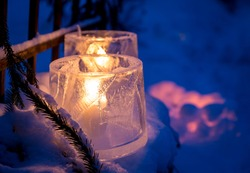 Ice lanterns, used as a Christmas outdoor decoration in Finland. On the blurred background, similar decoration made of snow. Shallow depth of field.