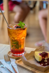 ice lemon tea mixed with blueberries and mulberry in a glass on the wood table in the coffee shop.