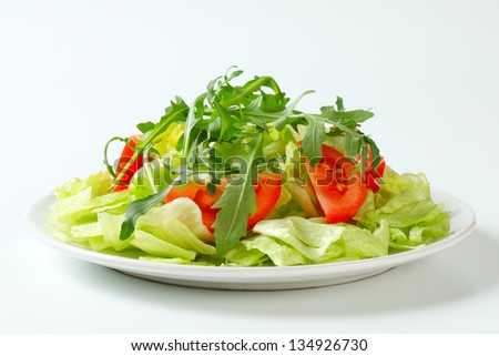 Ice lettuce leaves with tomato wedges and arugula
