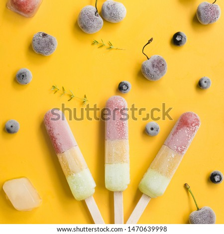 Ice lollies near blueberries and cherries