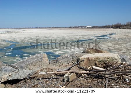 Ice melting near Lake Erie shoreline at beginning of spring thaw. Shot near Buffalo NY USA. Rocks, debris, and driftwood in foreground.