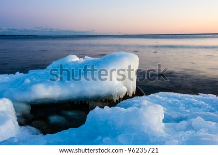 Ice melting on the beach in the sunset with open water in the background