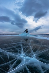 Ice of Lake Baikal in cracks near the island of Elenka at sunset under gray clouds. Wide panorama